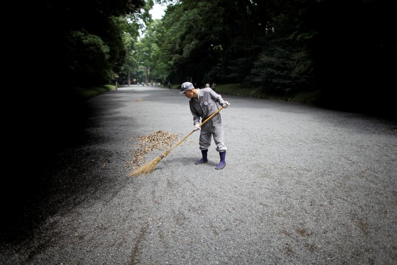 FILE PHOTO: A man sweeps the ground at a temple in Tokyo July 17, 2009.   REUTERS/Thomas White/File Photo