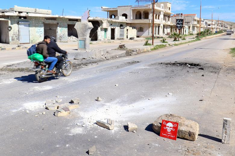 Men ride a motorbike past a hazard sign at a site hit by an airstrike on Tuesday in the town of Khan Sheikhoun in rebel-held Idlib, Syria April 5, 2017. The hazard sign reads, ''Danger, unexploded ammunition''. REUTERS/Ammar Abdullah