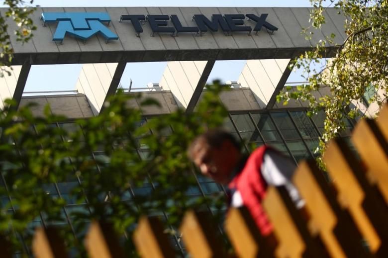 A man crosses a pedestrian bridge next to the headquarters of internet and fixed-line phone company Telmex, commercial brand of America Movil, in Mexico City, Mexico, March 9, 2017. REUTERS/Edgard Garrido