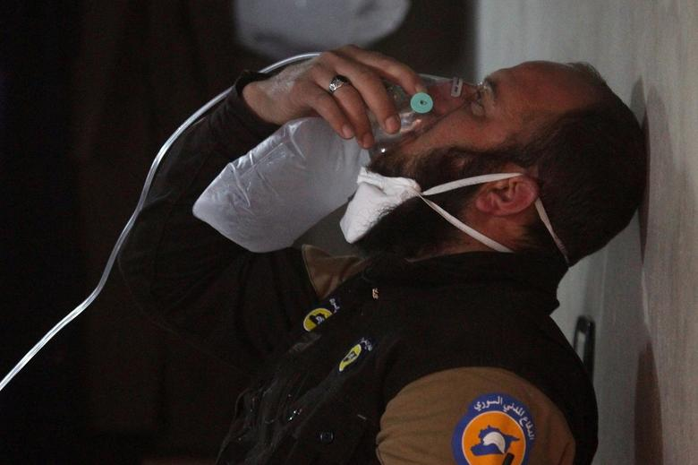 A civil defence member breathes through an oxygen mask, after what rescue workers described as a suspected gas attack in the town of Khan Sheikhoun in rebel-held Idlib. REUTERS/Ammar Abdullah