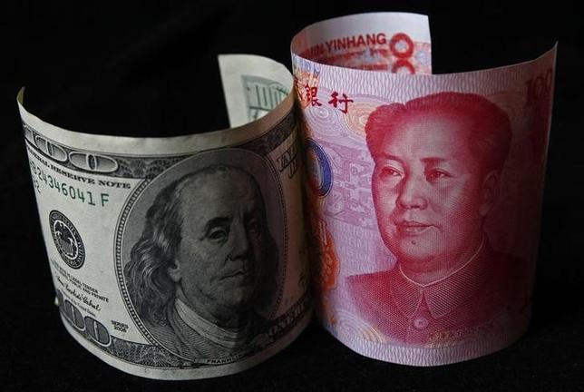 4月6日、米政府高官は6日、ロイターに対し、トランプ政権が貿易赤字の原因として、為替の「操作」よりも「不均衡」を重視していることを明らかにした。写真は米国と中国紙幣。2010年11月、北京で撮影(2017年 ロイター/Petar Kujundzic)
