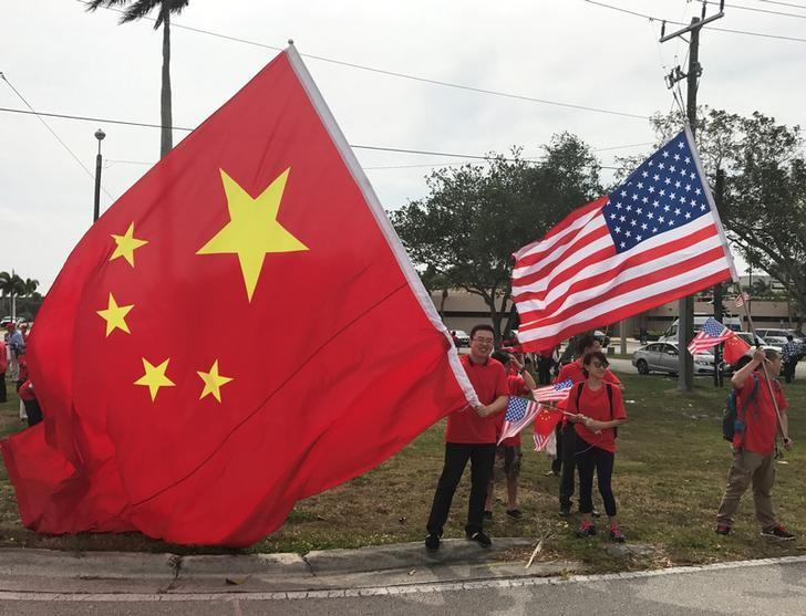 A group who identified themselves as China-U.S. Enterprise wait to view the motorcade of Chinese President Xi Jinping before his meeting with U.S. President Donald Trump at Palm Beach International Airport in West Palm Beach, Florida, U.S. April 6, 2017. REUTERS/Joe Skipper