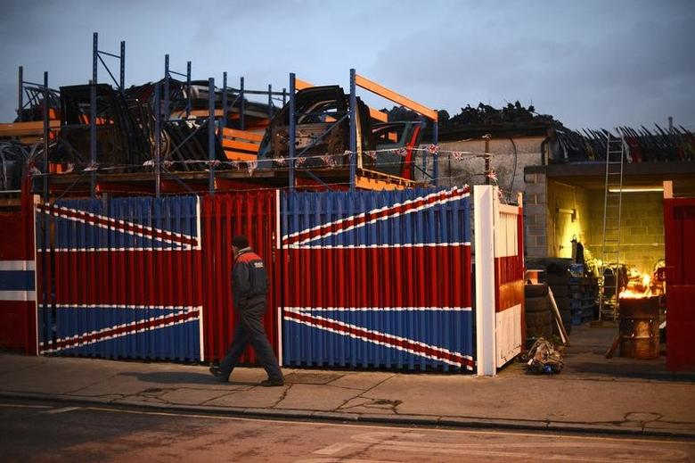 A man walks past a car scrap yard in east London January 25, 2013. REUTERS/Paul Hackett/Files