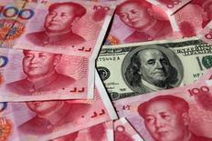 IMAGEN DE ARCHIVO: Billetes de 100 dólares está rodeado de billetes de 100 yuanes en Pekín, China.  16 de octubre 2010. Las reservas cambiarias chinas subieron levemente en marzo, pero un poco menos de lo que esperaba el mercado, debido a que medidas de control de capital y una apreciación del dólar contribuyeron a contener las salidas de divisas. REUTERS/Petar Kujundzic/File Photo