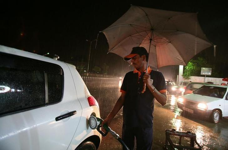 A worker fills a car with petrol at a fuel station as it rains in Jammu September 15, 2011. REUTERS/Mukesh Gupta/Files