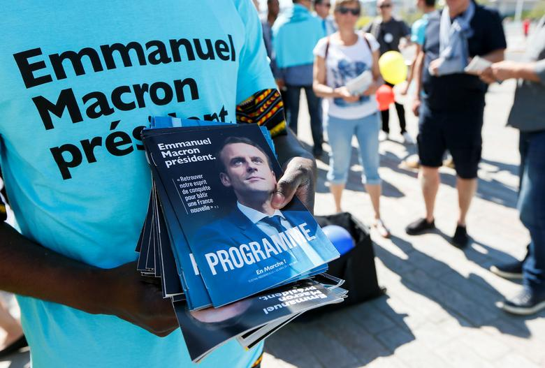 Supporters of Emmanuel Macron, head of the political movement En Marche !, or Onwards !, and candidate for the 2017 French presidential election, distribute political leaflets to support their candidate, in Lyon, France, April 9, 2017. REUTERS/Robert Pratta