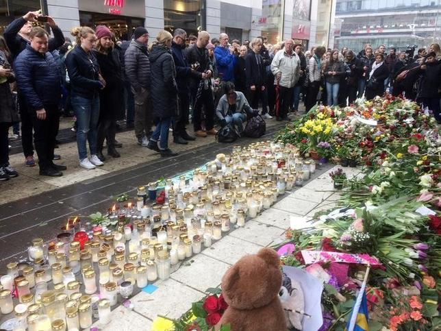 People look at flowers and candles next to Ahlens department store following Friday's attack in central Stockholm, Sweden, April 10, 2017. REUTERS/Gideon Malherbe