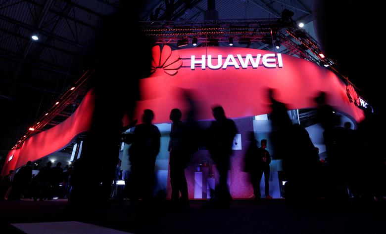 FILE PHOTO: Visitors walk past Huawei's booth during Mobile World Congress in Barcelona, Spain, February 27, 2017.  REUTERS/Eric Gaillard/File Photo