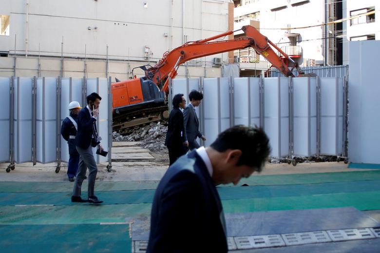 FILE PHOTO: Businessmen walk past heavy machinery at a construction site in Tokyo's business district, Japan, January 16, 2017.    REUTERS/Toru Hanai/File Photo