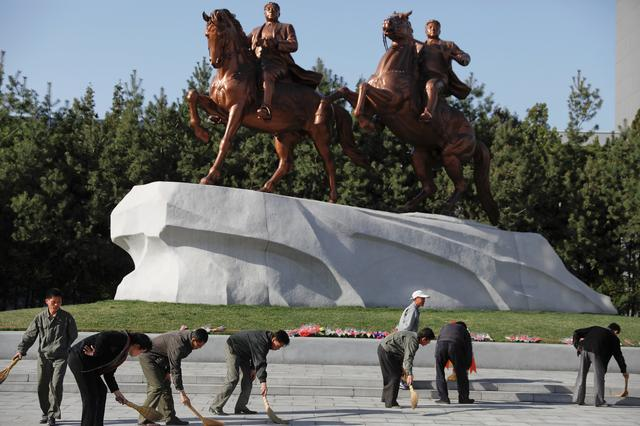 People sweep in front of statues of former North Korean leaders Kim Il Sung and Kim Jong Il in central Pyongyang, North Korea April 12, 2017. REUTERS/Damir Sagolj