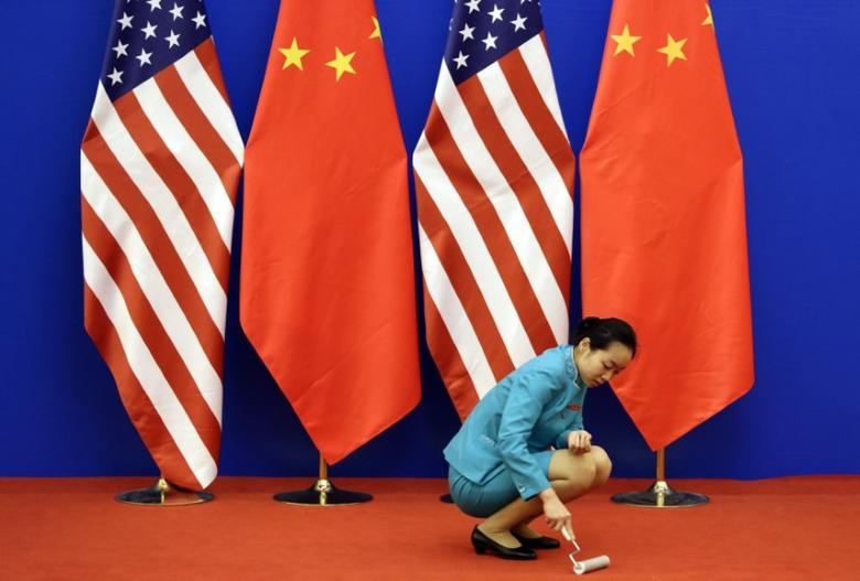 FILE PHOTO - An attendent cleans the carpet next to U.S. and Chinese national flags before a news conference for the 6th round of U.S.-China Strategic and Economic Dialogue at the Great Hall of the People in Beijing, July 10, 2014. REUTERS/Jason Lee