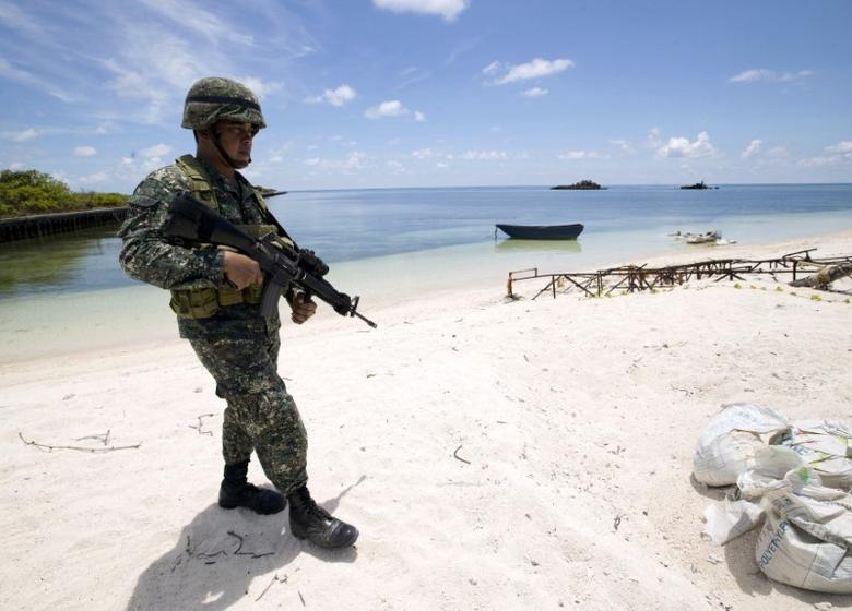 FILE PHOTO: A Filipino soldier patrols at the shore of Pagasa island (Thitu Island) in the Spratly group of islands in the South China Sea, west of Palawan, Philippines, May 11, 2015.        REUTERS/Ritchie B. Tongo/Pool/File Photo