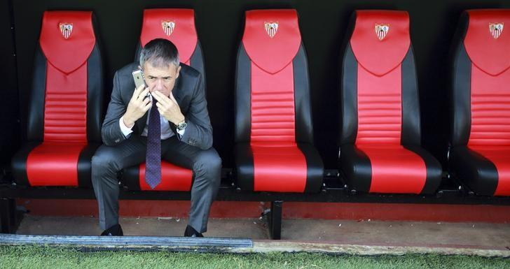 Levante's coach Lucas Alcaraz sits on the bench as he speaks on the mobile phone at the end of their Spanish First Division soccer match against Sevilla at Ramon Sanchez Pizjuan stadium in Seville, November 9, 2014. REUTERS/Marcelo del Pozo/Files