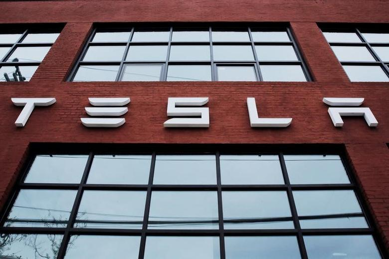 FILE PHOTO: A Tesla logo hangs on a building outside of a Tesla dealership in New York, U.S., April 29, 2016. REUTERS/Lucas Jackson/File Photo