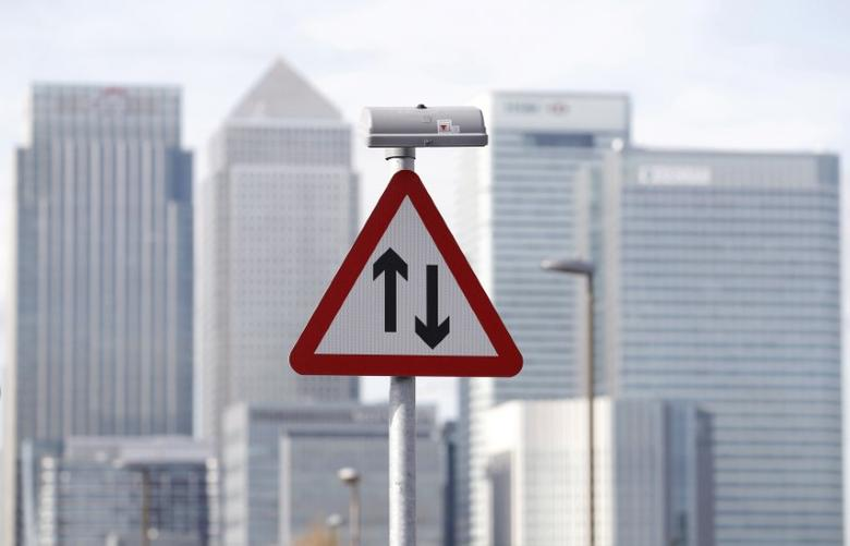 A traffic sign is pictured in front of the skyline of the the Canary Wharf financial district in London October 21, 2010. REUTERS/Luke MacGregor