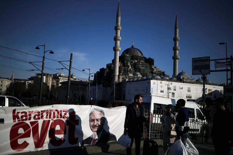 People make their way on Galata bridge next to a banner depicting Turkish Prime Minister Binali Yildirim, with the New Mosque in the background, in Istanbul, Turkey, April 13, 2017. The banner reads ''Our decision is Yes''. REUTERS/Alkis Konstantinidis