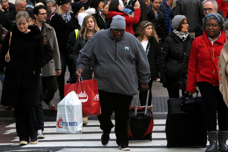 A woman carries purchases across 34th Street in Manhattan, New York, U.S., November 25, 2016.  REUTERS/Andrew Kelly/Files