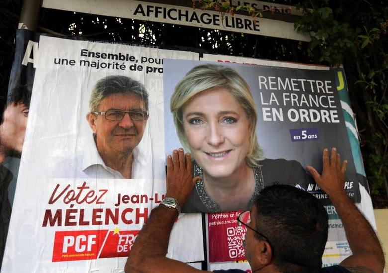 Sauveur, a member of the French National Front (FN) political party pastes a poster on a free  billboard for French National Front (FN) political party leader Marine Le Pen as part of the 2017 French presidential election campaign in Antibes, France, April 14, 2017.   REUTERS/Eric Gaillard