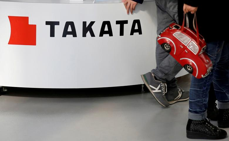 FILE PHOTO: Visitors walk past a logo of Takata Corp on its display at a showroom for vehicles in Tokyo, Japan February 5, 2016. REUTERS/Toru Hanai/File Photo