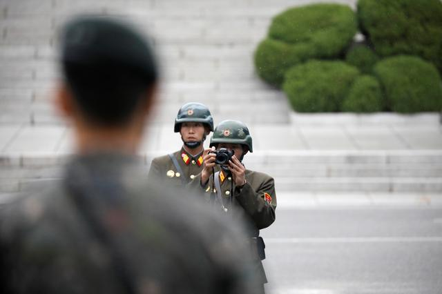 A North Korean soldier takes photographs as U.S. Vice President Mike Pence (not pictured) arrives at the truce village of Panmunjom, South Korea, April 17, 2017.  REUTERS/Kim Hong-Ji