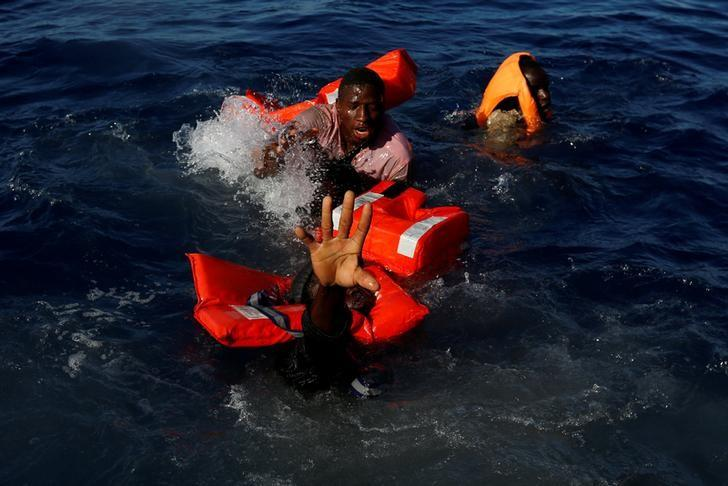 Migrants try to stay afloat after falling off their rubber dinghy during a rescue operation by the Malta-based NGO Migrant Offshore Aid Station (MOAS) ship in the central Mediterranean in international waters some 15 nautical miles off the coast of Zawiya in Libya, April 14, 2017.    REUTERS/Darrin Zammit Lupi