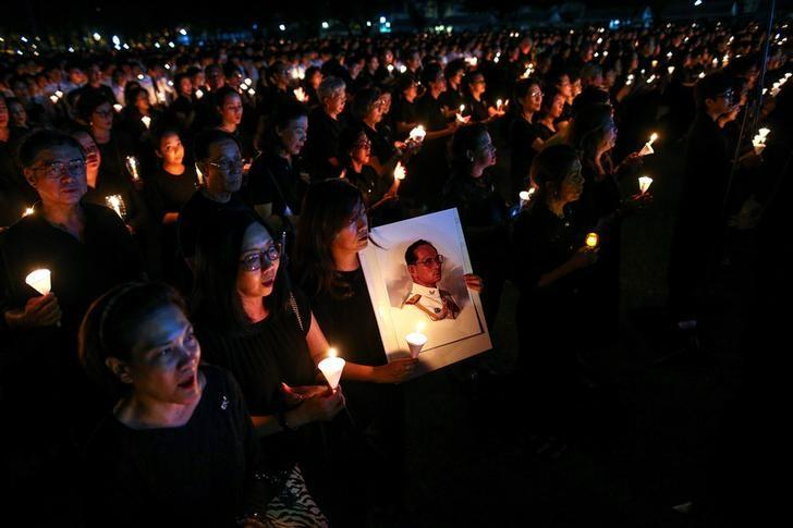 A mourner holds up a picture of Thailand's late King Bhumibol Adulyadej as she gathers with others during a vigil to mark his birthday, at a university in Bangkok, Thailand December 5, 2016. REUTERS/Athit Perawongmetha