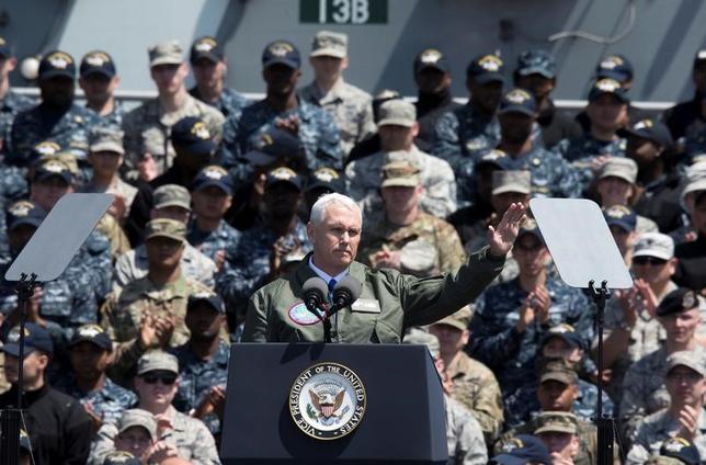 4月19日、来日中のペンス米副大統領は、北朝鮮に対し同盟国および中国と経済・外交面で圧力をかける決意を示した。ただ、いかなる攻撃にも「圧倒的な力」で対抗すると付け加えた。写真は空母ロナルド・レーガンで手を振る同副大統領。横須賀での代表撮影(2017年/ロイター)