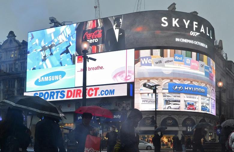 FILE PICTURE: Shoppers pass an advertisement for the James Bond film, Skyfall, on the electronic screens at Piccadilly Circus in central London October 21, 2012. REUTERS/Toby Melville
