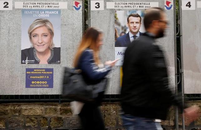 4月19日、フランス政治研究センター(CEVIPOF)がルモンド紙の委託で実施した世論調査によると、23日に行われる仏大統領選第1回投票の支持率は、中道系独立候補のマクロン前経済相と極右政党・国民戦線(FN)のルペン党首が他候補に対するリードを僅かに保っている。写真はパリ市内の選挙ポスター。10日撮影(2017年 ロイター/GONZALO FUENTES)