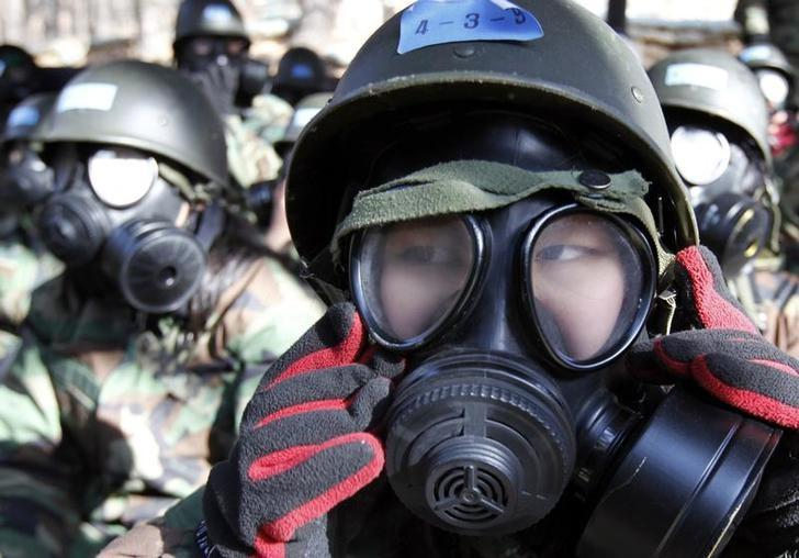 Students wear gasmasks before entering a building where they will be exposed to tear gas as part of their chemical, biological and radiological training during a winter military boot camp at a military unit in Bucheon, west of Seoul January 20, 2011. REUTERS/Lee Jae-Won