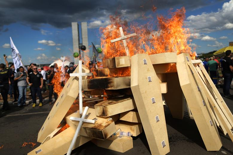 Striking police officers set fire to coffins during a protest by Police officers from several Brazilian states against pension reforms proposed by Brazil's president Michel Temer, in Brasilia, Brazil. REUTERS/Adriano Machado
