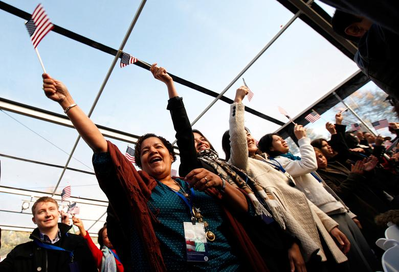 New U.S. citizens celebrate after taking the oath of citizenship during a naturalization ceremony beneath the Statue of Liberty during ceremonies marking the 125th anniversary of the Statue at Liberty Island in New York, October 28,  2011.  REUTERS/Mike Segar/File Photo