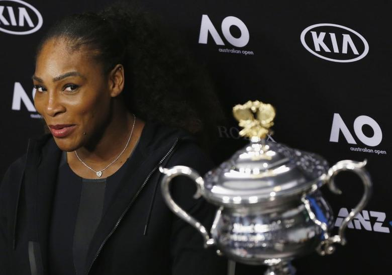 Serena Williams of the U.S. reacts next to the Women's singles trophy during her post-match news conference. REUTERS/Issei Kato