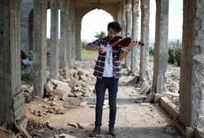 Ameen Mukdad, un violinista de Mosul que vivió bajo el régimen de Estado Islámico por dos años y medio y sufrió la destrucción de sus instrumentos musicales, realiza un pequeño concierto en el santuario de Nabi Yunus en el este de Mosul, Irak, 19 de abril de 2017. En medio de las ruinas bombardeadas de un antiguo lugar venerado por musulmanes y cristianos en Mosul, el violinista iraquí Ameen Mukdad realizó el miércoles un pequeño concierto en la ciudad de la que huyó obligado por milicianos de Estado Islámico. REUTERS/Muhammad Hamed