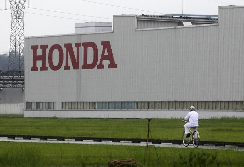 A worker rides a bicycle past a Honda auto parts manufacturing plant in Foshan, Guangdong province, China June 2, 2010.  REUTERS/Stringer