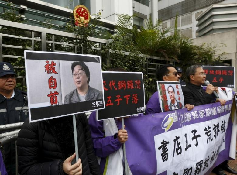 Members from the pro-democracy Civic Party carry a portrait of Gui Minhai (L) and Lee Bo during a protest outside the Chinese Liaison Office in Hong Kong, China January 19, 2016. REUTERS/Bobby Yip