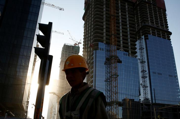 A worker walks past a construction site in the Central Business District in Beijing, China, April 18, 2017.  REUTERS/Thomas Peter
