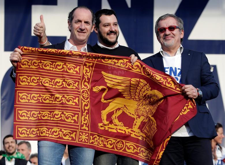 FILE PHOTO: Northern League party leader Matteo Salvini (C) poses with the Lion of Saint Mark flag, with politicians Luca Zaia (L) and Roberto Maroni, during a rally downtown Rome, February 28, 2015. REUTERS/Max Rossi/File Photo