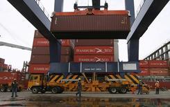 Una grúa descargando un contenedor sobre un camión en el puerto colombiano de Cartagena, mayo 14, 2012.  Colombia redujo el déficit en su balanza comercial en febrero a 816,6 millones de dólares, desde un rojo de 1.001,6 millones de dólares en igual mes del año pasado, por un repunte de las exportaciones, informó el jueves el Departamento Nacional de Estadísticas (DANE).  REUTERS/Joaquin Sarmiento