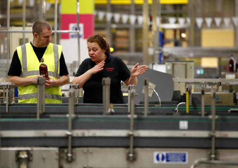 Workers talk to each other on the production line at the Diageo owned Shieldhall bottling plant in Glasgow, Scotland March 24, 2011. REUTERS/David Moir