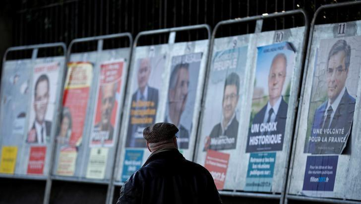A man looks at campaign posters of the 11th candidates who run in the 2017 French presidential election in Enghien-les-Bains, near Paris, France April 19, 2017.   REUTERS/Christian Hartmann