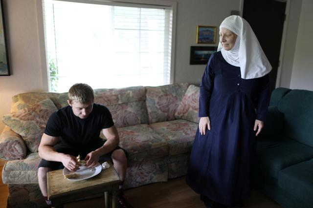 California ''weed nun'' Christine Meeusen, 57, who goes by the name Sister Kate (R), talks to her son Alex as he eats lunch at Sisters of the Valley near Merced, California, U.S., April 18, 2017.  REUTERS/Lucy Nicholson