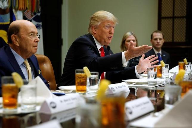 4月20日、トランプ米大統領は、中国など外国製の鉄鋼製品が、自国企業や安全保障に脅威を及ぼすかを判断するため、調査に着手した。写真は同大統領(中央)とロス商務長官(左)。2月撮影(2017年 ロイター/Jonathan Ernst)