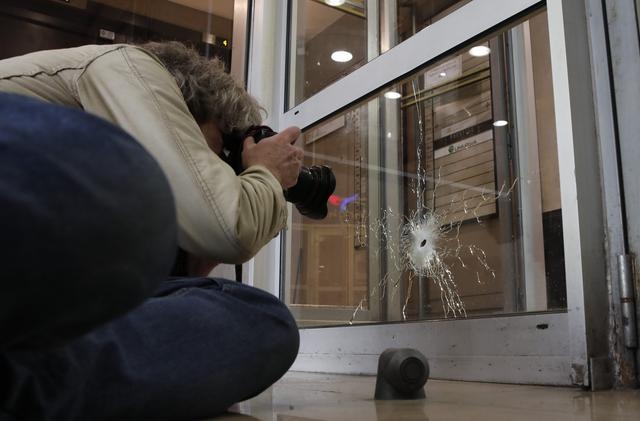 A photographer takes pictures of a damaged window on the Champs Elysees Avenue the day after a policeman was killed and two others were wounded in a shooting incident in Paris, France, April 21, 2017. REUTERS/Benoit Tessier