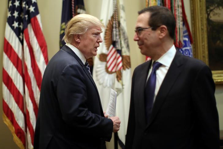U.S. President Donald Trump attends a listening session with CEOs of small and community banks, accompanied by Secretary of the Treasury Steven Mnuchin (R), at the White House in Washington, U.S., March 9, 2017.  REUTERS/Carlos Barria