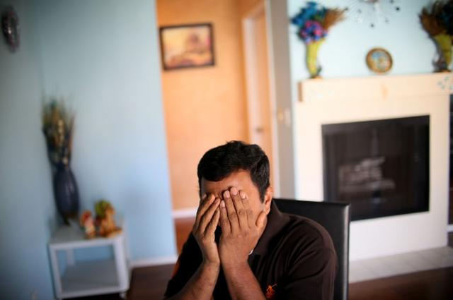 Raj, an immigrant from Sri Lanka, sits in his apartment in San Diego, California, U.S., April 9, 2017. REUTERS/Sandy Huffaker