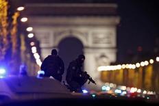 اثنان من أفراد الشرطة يقفون فوق سيارتهما في موقع هجوم باريس يوم الخميس. تصوير: كريستيان هارتمان - رويترز