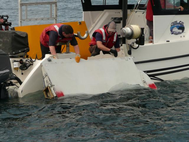 A Boeing 777 flaperon cut down to match the one from flight MH370 found on Reunion island off the coast of Africa in 2015, is lowered into water to discover its drift characteristics by Commonwealth Scientific and Industrial Research Organisation researchers in Tasmania, Australia, in this handout image taken March 23, 2017. CSIRO/Handout via REUTERS