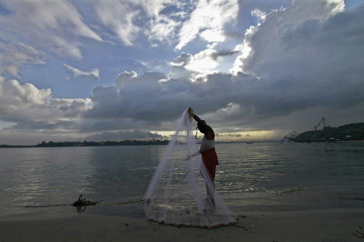 A fisherman arranges his fishing net at a beach in Kochi June 5, 2014. REUTERS/Sivaram V/Files