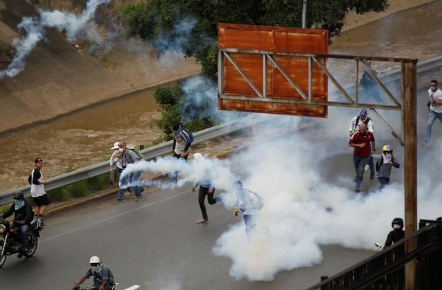 Demonstrators run away from tear gas during clashes with police while rallying against Venezuela's President Nicolas Maduro in Caracas, Venezuela, April 20, 2017. REUTERS/Christian Veron